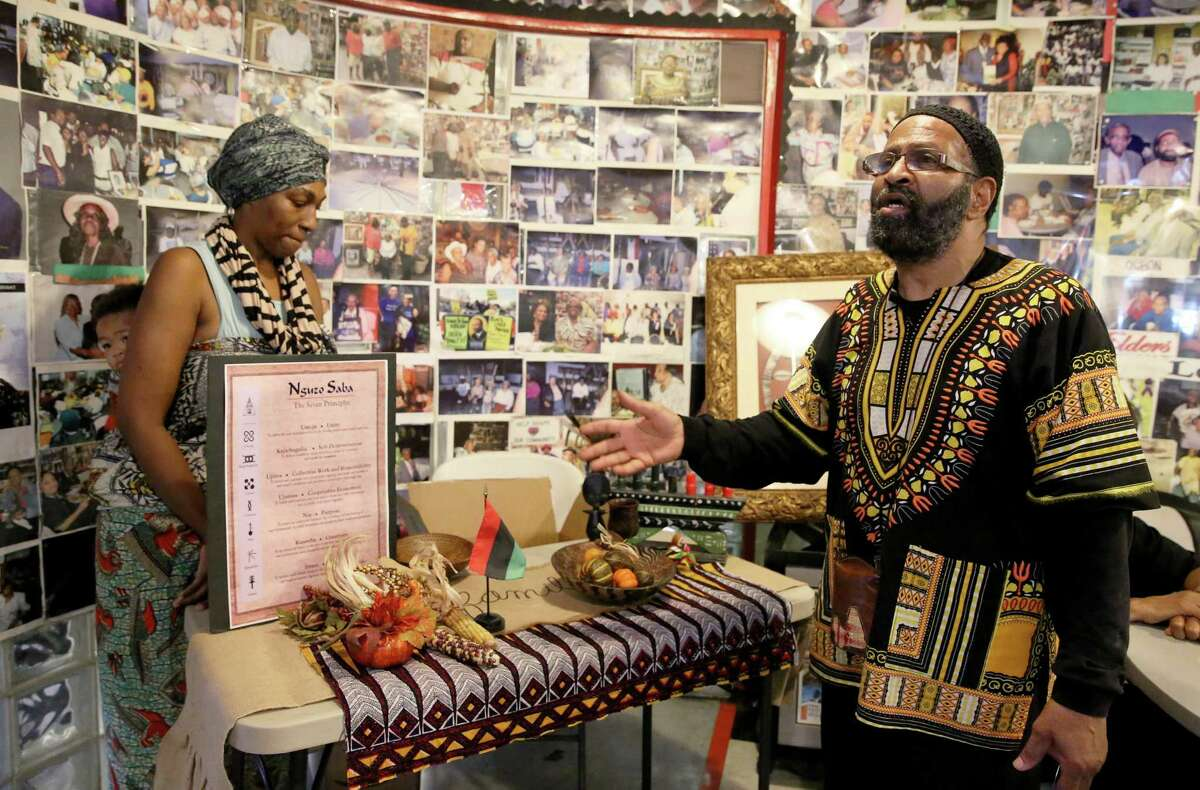 Deloyd Parker, executive director of the SHAPE Community Center for 47 years, encourages people to start celebrating the principles of Kwanzaa after setting up an altar on Saturday.
