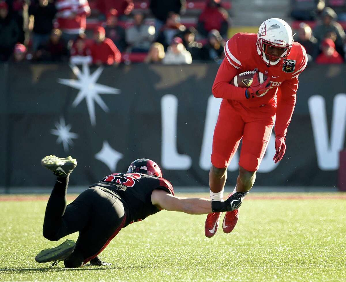 San Diego State safety Parker Baldwin, left, trips up UH wide receiver Linell Bonner during the second half of Saturday's Las Vegas Bowl. Bonner and his teammates couldn't get much going on offense in the second half.