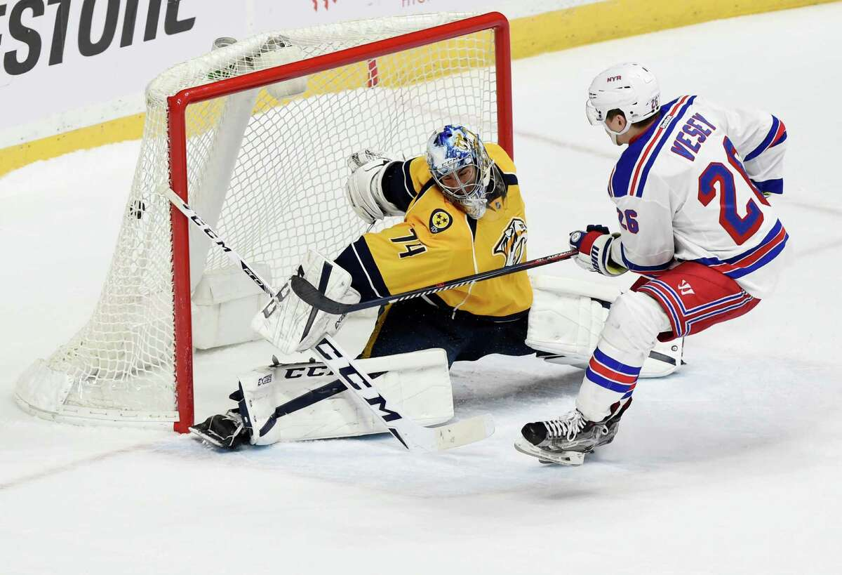 New York Rangers left wing Jimmy Vesey (26) beats Nashville Predators goalie Juuse Saros (74), of Finland, for a shootout goal at an NHL hockey game Saturday, Dec. 17, 2016, in Nashville, Tenn. The goal would end up being the game-winner. (AP Photo/Sanford Myers) ORG XMIT: TNSM112