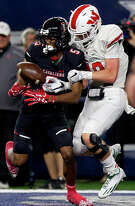 Lake Travis wide receiver Garrett Wilson (5) hauls in a 5-yard touchdown pass from quarterback Charlie Brewer (16) as The Woodlands defensive back Quinn Binney (19) defends during the first quarter of a UIL Class 6A Division I state final at AT&T Stadium Saturday, Dec. 17, 2016, in Arlington.