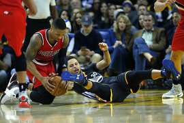 Portland Trail Blazers guard Damian Lillard (0) grabs the ball after Golden State Warriors guard Stephen Curry (30) loses his balance during the second half of an NBA basketball game between the Golden State Warriors and the Portland Trail Blazers at Oracle Arena on Saturday, Dec. 17, 2016 in Oakland, Calif. Warriors won 135-90.