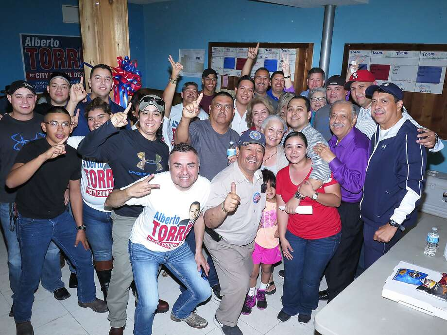 City Council District IV candidate Alberto Torres, center right, celebrates with supporters at his campaign headquarters after taking the lead in early voting results Saturday. Photo: Cuate Santos /Laredo Morning Times / Laredo Morning Times