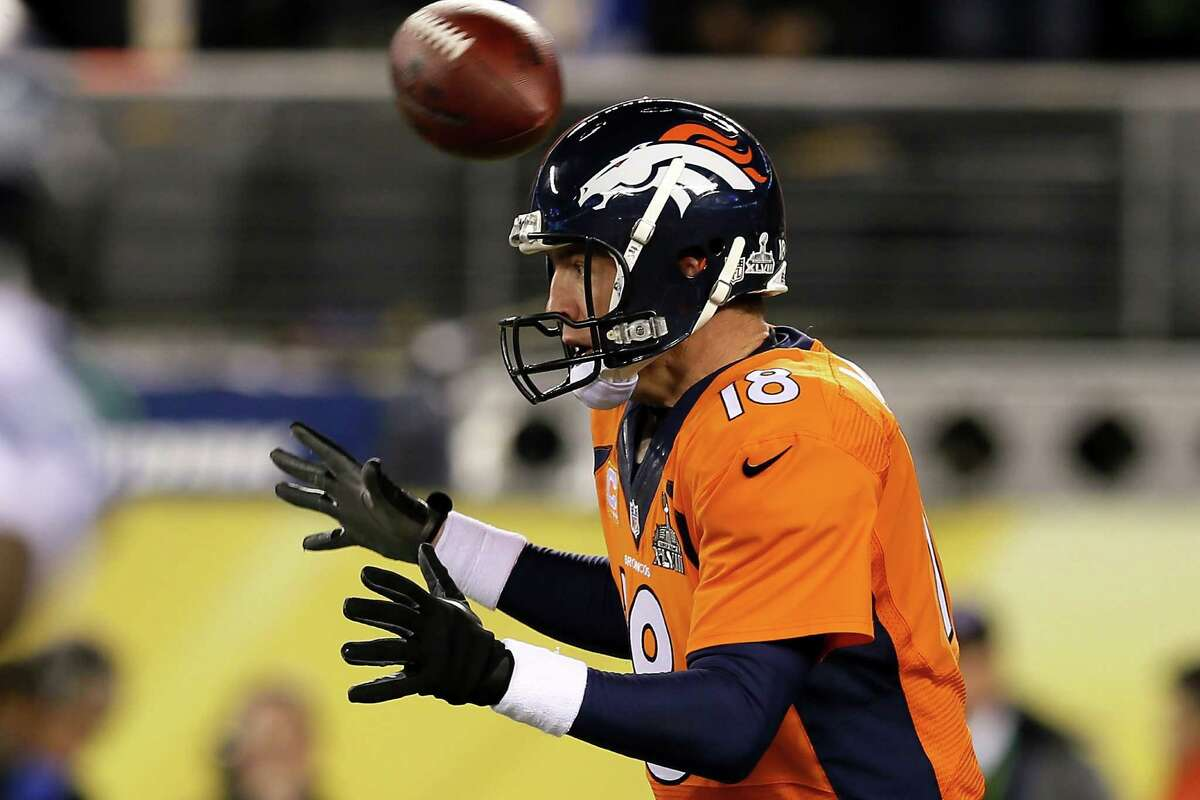 EAST RUTHERFORD, NJ - FEBRUARY 02: The ball flies over the head of quarterback Peyton Manning #18 of the Denver Broncos in the first quarter against the Seattle Seahawks during Super Bowl XLVIII at MetLife Stadium on February 2, 2014 in East Rutherford, New Jersey. (Photo by Kevin C. Cox/Getty Images)