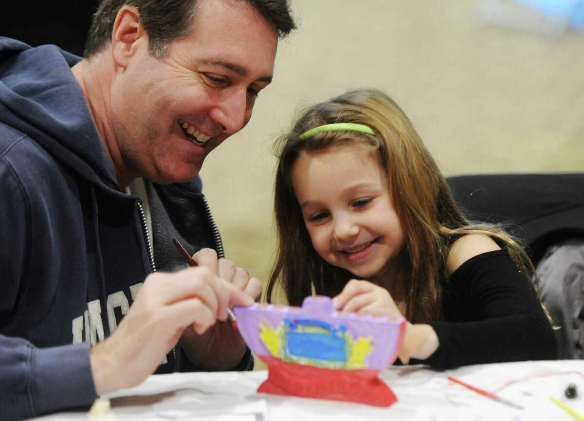 Stu Slotnick, of Rye Brook, N.Y., and his daughter, Julia, 6, paint a menorah during the annual Chanukah Party at Temple Sholom in Greenwich, Conn. Sunday, Dec. 18, 2016. The