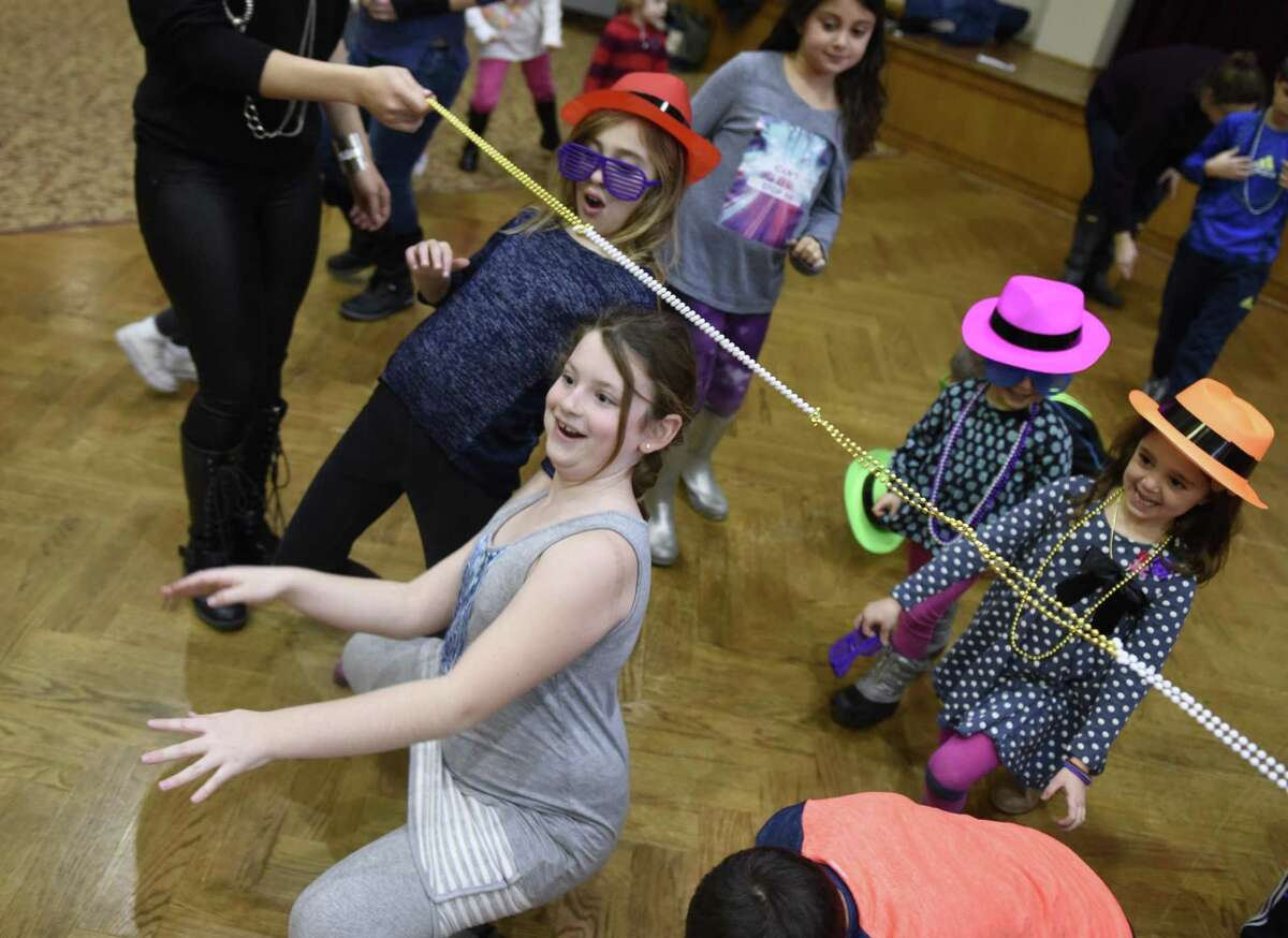 Saide Kessler, 9, of Greenwich, gets low during a game of limbo at the annual Chanukah Party at Temple Sholom in Greenwich, Conn. Sunday, Dec. 18, 2016. The