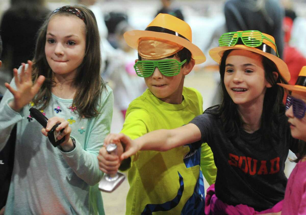Ten-year-olds Maya Bodek, left, of Stamford, Ryan Kauffman, of Greenwich, and Kate Friedman, of Greenwich, hit their buzzers to answer a question during Chanukah Jeopardy at the annual Chanukah Party at Temple Sholom in Greenwich, Conn. Sunday, Dec. 18, 2016. The
