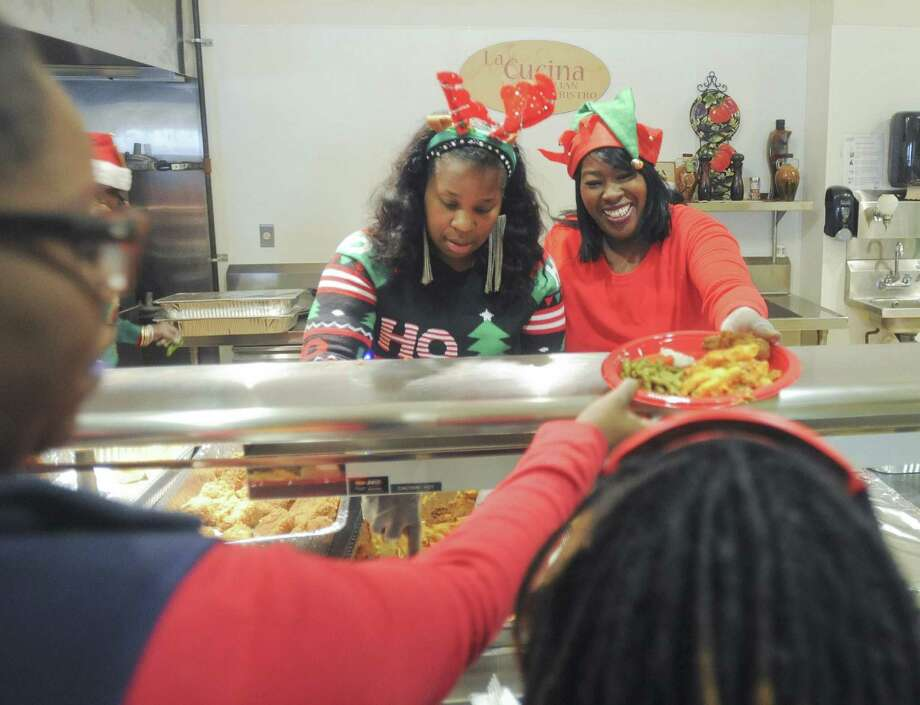 Trenace Ruffin and Rachel Jones, volunteers of the Norwalk-based church, House of Prophecies and Prayer, help serve food at the Brien McMahon High School cafeteria. Saturday, Dec. 17, 2016 Photo: Scott Mullin / For Hearst Connecticut Media / The News-Times Freelance