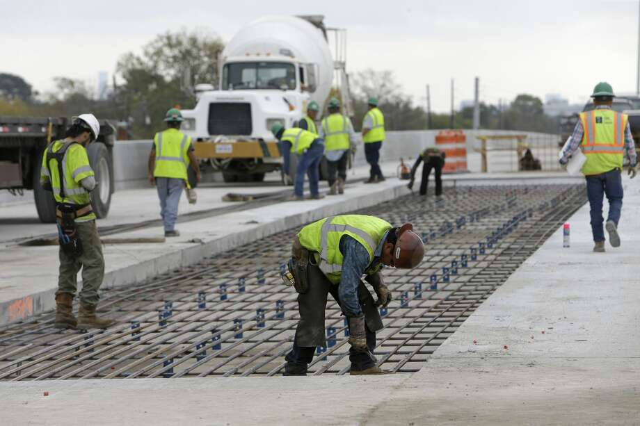 Workers tie rebar along the U.S. 290 westbound main lanes on Dec. 13. Photo: Melissa Phillip/Houston Chronicle