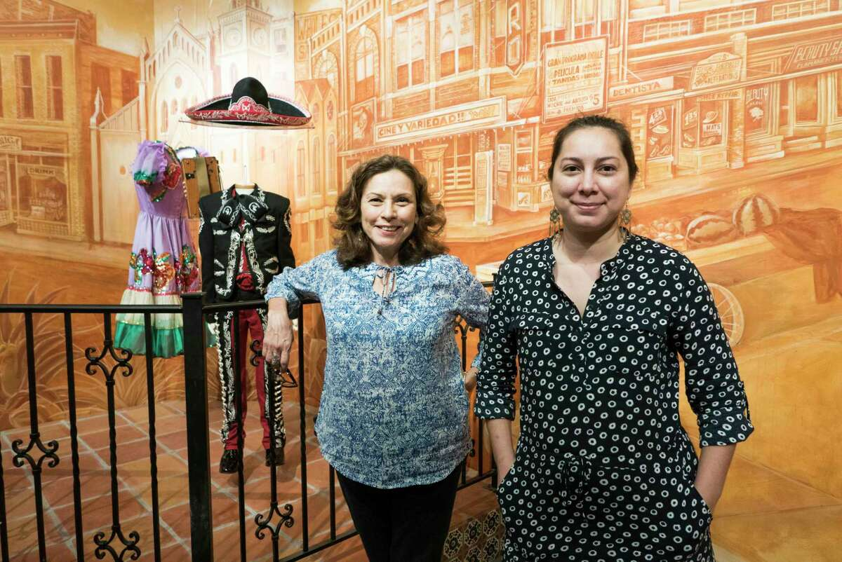 """Curators Lupita Barrera, left, and Sarah Gould stand in the interactive exhibition """"Los Tejanos"""" at the Institute of Texan Cultures on Thursday, May 14, 2015. The new exhibit explores the history, culture and contributions of Tejanos. The mariachi suit behind them was worn by Sebastien De la Cruz, the young singer who was the target of hateful comments after singing the national anthem before a San Antonio Spurs championship series game in 2013. The dress was worn by singer Lydia Mendoza, who performed and recorded many Tejano and conjunto hits before she died in 2007. The mural mural was painted by Adriana M. Garcia and Yenifer Gavina with assistance by Erica De la Rosa, Michelle McFarlin and Ernesto Cuevas Jr."""