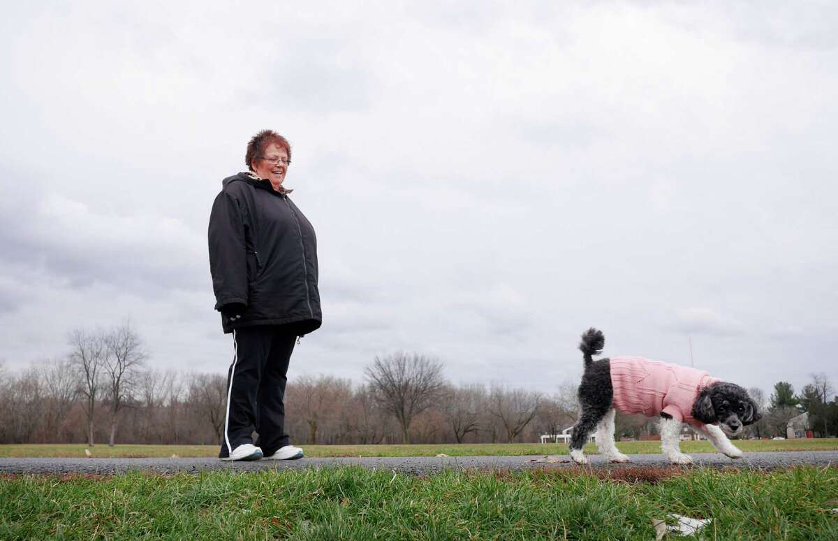 Linda Moon of Troy takes a walk with her dog, Allie, a parti poodle, through Schuyler Flatts Park on Sunday, Dec. 18, 2016, in Watervliet, N.Y. Moon took in Allie two years ago, getting her through Heaven Sent Animal Rescue. (Paul Buckowski / Times Union)