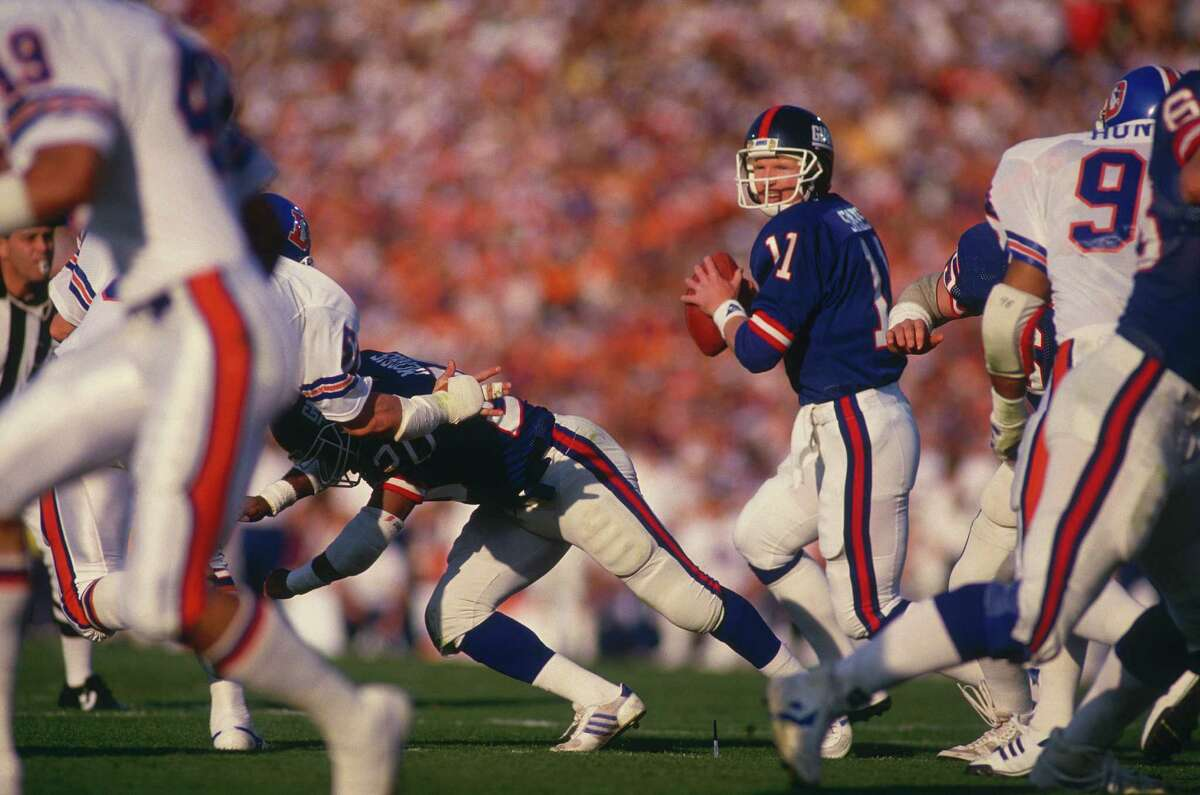 PASADENA, CA - JANUARY 25: New York Giants quarterback Phil Simms #11 runs and looks for receiver during Super Bowl XXI against the Denver Broncos at the Rose Bowl on January 25, 1987 in Pasadena, California. The Giants defeated the Broncos 39-20. (Photo by Focus on Sport/Getty Images)
