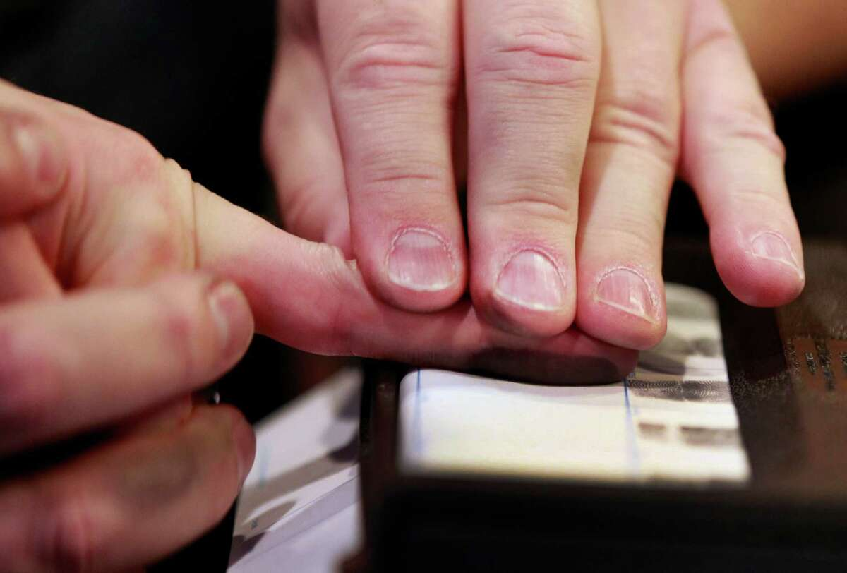 """PROVO, UT - DECEMBER 19: Fingerprints are recorded at a gun concealed carry permit class put on by """"USA Firearms Training"""" on December 19, 2015 in Provo, Utah. (Photo by George Frey/Getty Images)"""
