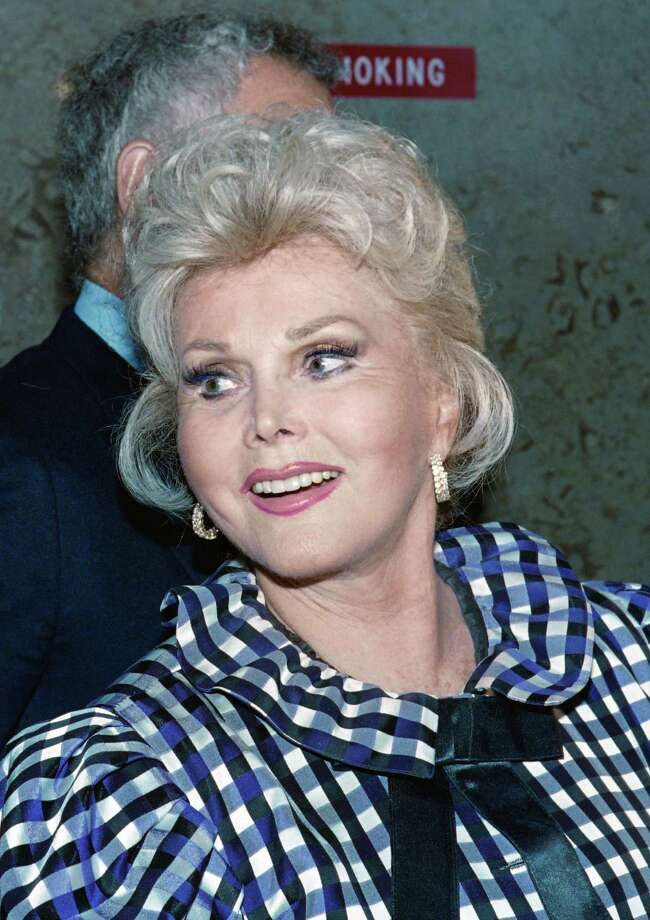 "(FILES) This file photo taken on July 12, 1989 shows US actress Zsa Zsa Gabor exiting the Beverly Hills Municipal Court on July 12, 1989 where she appeared in order to answer charges of battery against a police officer. Zsa Zsa Gabor, the Hungarian-born Hollywood siren perhaps better known for her prodigious love life than her movie credits, died Sunday, December 18, 2016 after suffering a heart attack, her husband said. An emotional Frederic von Anhalt told AFP that Gabor had passed away at home surrounded by friends and family. ""Everybody was there. She didn't die alone,"" he told AFP by telephone, choking back sobs. She was 99.  / AFP PHOTO / HAL GARBHAL GARB/AFP/Getty Images Photo: HAL GARB, Stringer / AFP or licensors"