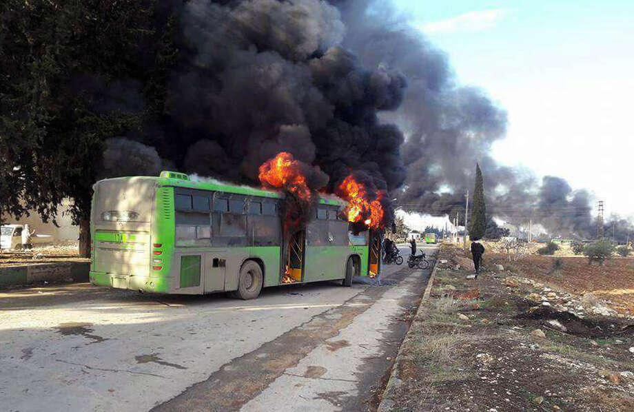In this photo released by the Syrian official news agency SANA, smoke rises in green government buses, in Idlib province, Syria, Sunday, Dec. 18, 2016. Activists said, militants have burned at least five buses assigned to evacuate wounded and sick people from two villages in northern Syria. The incident could scuttle a wider deal that encompasses the evacuation of thousands of trapped rebel fighters and civilians from the last opposition foothold in east Aleppo. (SANA via AP) Photo: Uncredited, HOGP / SANA