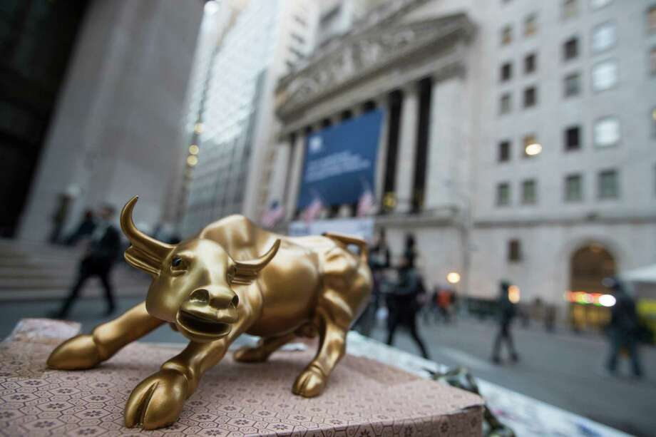 """A miniature reproduction of Arturo Di Modica's """"Charging Bull"""" sculpture sits on display at a street vendor's table outside the New York Stock Exchange, in lower Manhattan.  Photo: Mary Altaffer, STF / Copyright 2016 The Associated Press. All rights reserved."""