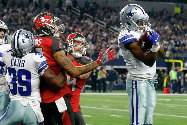 Dallas Cowboys' Brandon Carr (39) helps defend as Byron Jones, right, intercepts a pass intended for Tampa Bay Buccaneers' Mike Evans, center left, in the first half of an NFL football game, Sunday, Dec. 18, 2016, in Arlington, Texas.
