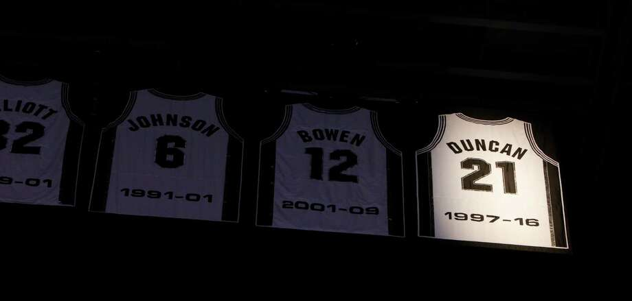 San Antonio Spurs great Tim Duncan and his children watch the No. 21 of one of the NBA's greatest power forwards get raised to the AT&T Center rafters for retirement  Sunday night. Photo: Ronald Cortes, Stringer / 2016 Getty Images