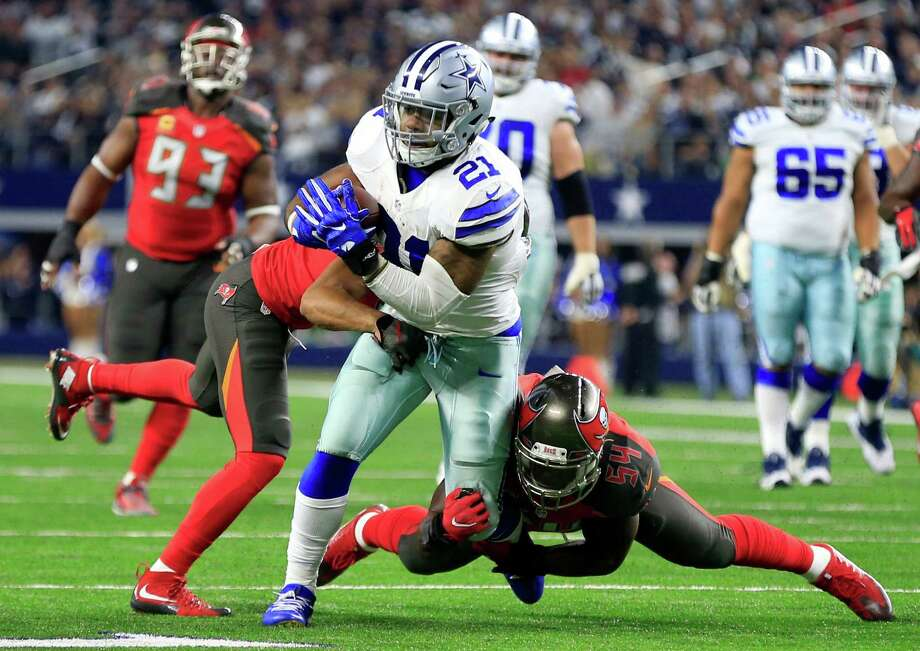 Dallas Cowboys running back Ezekiel Elliott (21) is wrapped up by Tampa Bay Buccaneers' Javien Elliott, left, and Lavonte David (54) after a short run in the first half of an NFL football game, Sunday, Dec. 18, 2016, in Arlington, Texas. (AP Photo/Ron Jenkins) Photo: Ron Jenkins, FRE / FR171331 AP