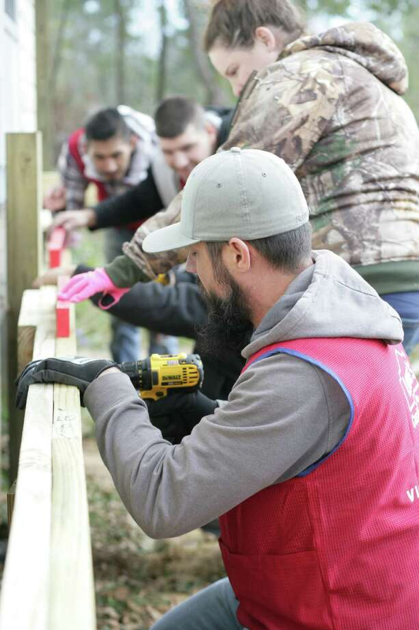 Lowe's employees Robert Volpe, Adrian Keller, Michael McClain, Jimmy Salazar screw in a header board that will support a new deck on a home owned by Heaven's Army. Photo: Vanesa Brashier