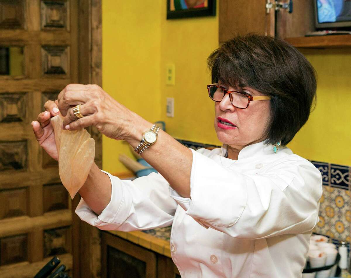 Sylvia Casares, owner of Sylvia's Enchilada Kitchen restaurants, demonstrates how to trim slightly oversized husks to size during a tamale-making class. Casares will offer make-your-own-tamale parties (tamaladas) on Dec. 22 and 23 at both her 6401 Woodway and 1140 Eldridge Parkway restaurants.