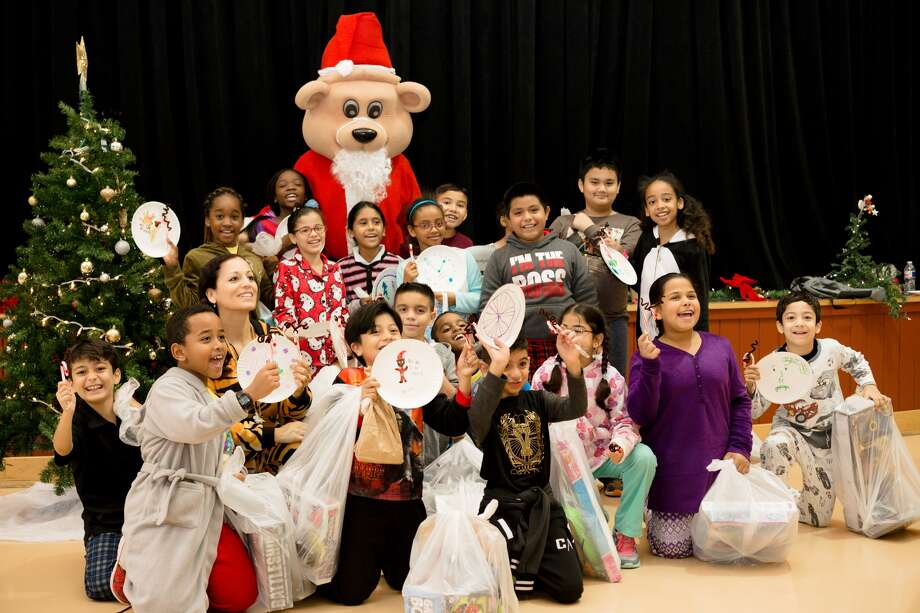 Kelsey-Seybold Clinic's mascot, KelseyBear, and volunteers went to the Neighborhood Centers Baker-Ripley Charter School's annual Christmas party. They surprised the children with bags of toys and books. Photo credit:Elliott Tate, Kelsey-Seybold Clinic