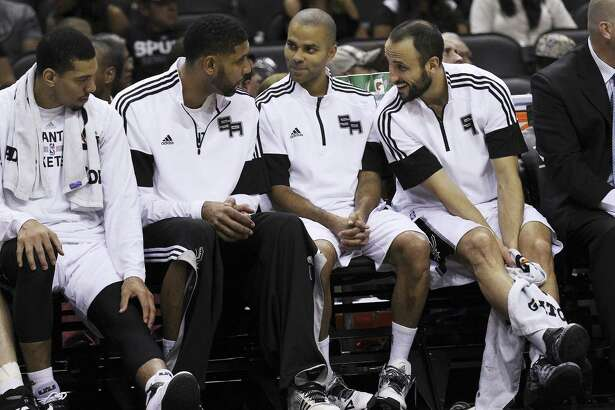 Danny Green, Tim Duncan, Tony Parker and Manu Ginobili rest on the bench in October 2014.