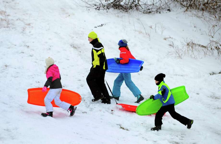 Kids have a great time sledding on the hill at Sturges Park in Fairfield, Conn., on Saturday Dec. 17, 2016. The snow that began falling before 5 a.m., left several inches of snow across Connecticut before it tapered off into rain. Photo: Christian Abraham / Hearst Connecticut Media / Connecticut Post