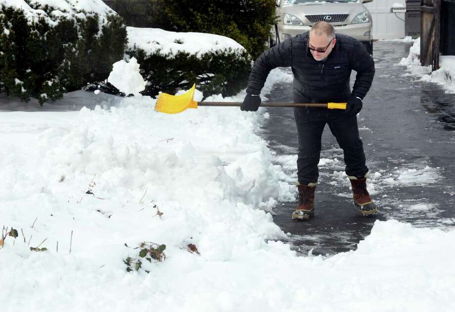 Jamie Walsh shovels snow in his driveway at his home on Gorham Avenue in Westport, Conn., on Saturday Dec. 17, 2016. The snow that began falling before 5 a.m., left several inches of snow across Connecticut before it tapered off into rain. Photo: Christian Abraham / Hearst Connecticut Media / Connecticut Post
