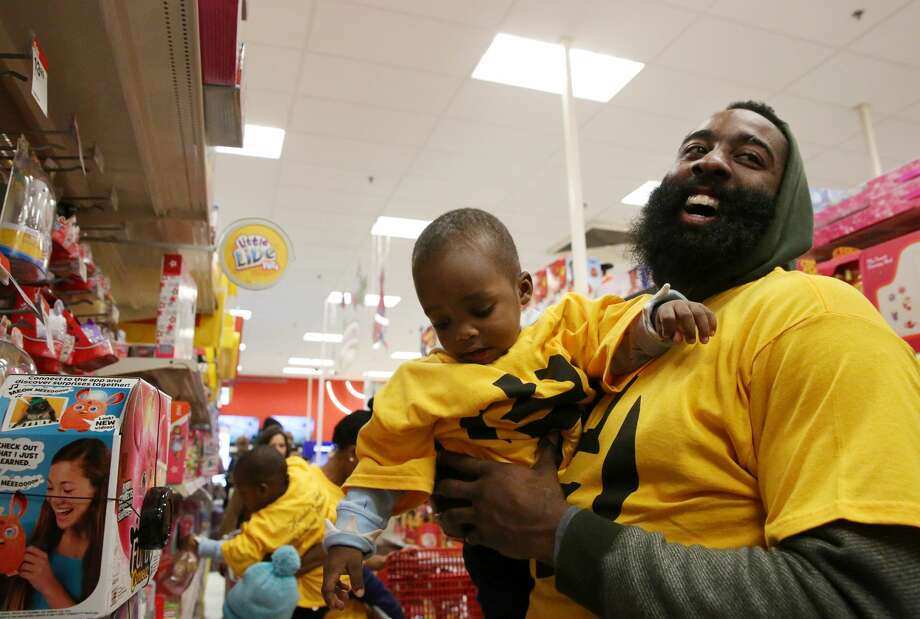 Houston Rockets star James Harden holds Noah Layton, 2, in his arms while helping Noah to pick a Christmas present for himself at a Target store Sunday, Dec. 18, 2016, in Houston. This year marked the fifth year that James Harden Family Foundation taking Houston area single mothers and their children on shopping for both holiday wish list items and daily necessity. Twenty-one families were chosen to participate this year. ( Yi-Chin Lee / Houston Chronicle ) Photo: Yi-Chin Lee/Houston Chronicle