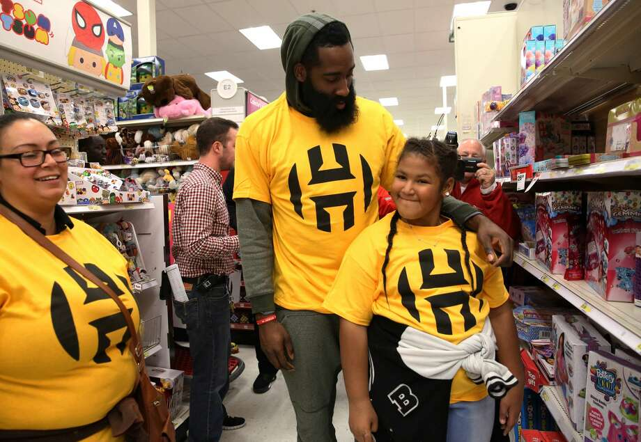 Houston Rockets star James Harden comforts Jenesis, 9, after finding out that the store has run out of Crayola Air Marker Sprayer, an item she wants for Christmas present, at a Target store Sunday, Dec. 18, 2016, in Houston. For the fifth year, the foundation took Houston area single mothers and their children on shopping for both holiday wish list items and daily necessity. Twenty-one families were chosen to participate this year. ( Yi-Chin Lee / Houston Chronicle ) Photo: Yi-Chin Lee/Houston Chronicle
