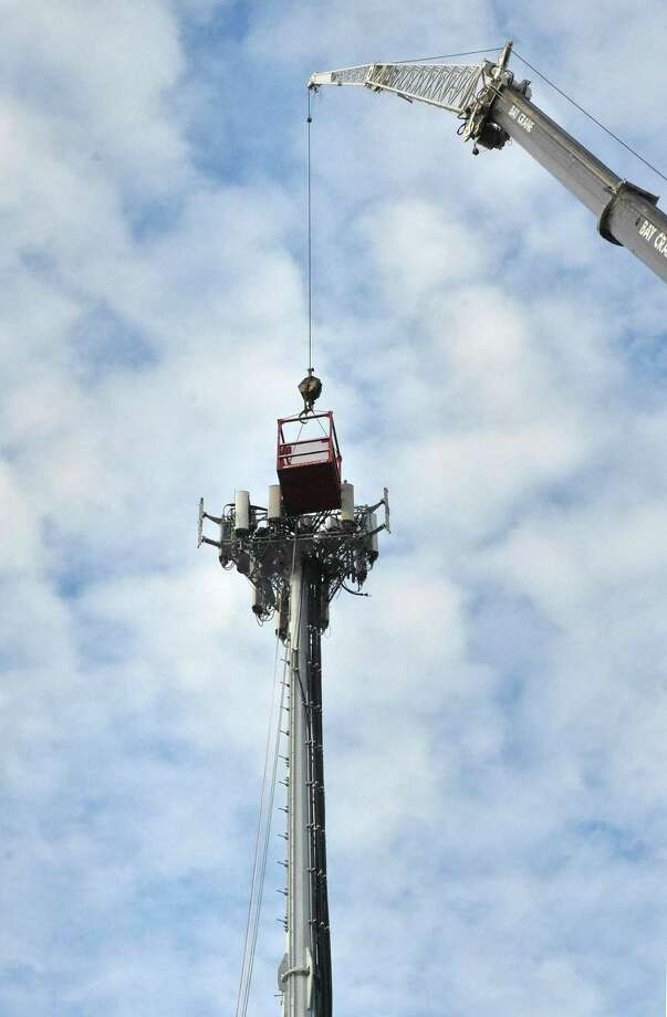 Workers access a cell tower with a crane along Connecticut Ave. in Norwalk Conn. in December 2016. In an effort to reduce the need for tower installations, mobile service providers have been installing small transmitters on utility poles to improve local coverage. Photo: Alex Von Kleydorff / Hearst Connecticut Media / Connecticut Post