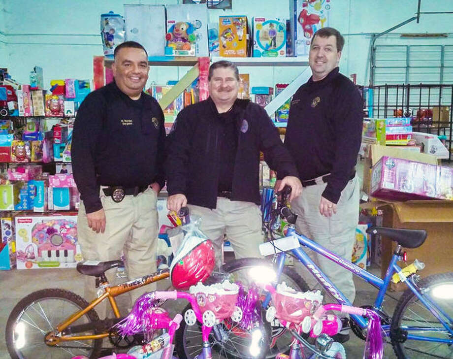 Among citiy employees helping to assemble bicycles for the Christmas Angel projec were, from left: Sgt. Marty Morales, Assistant Police Chief Scott Schultz and Lt. Todd Zettlemoyer. Photo: City Of Sugar Land