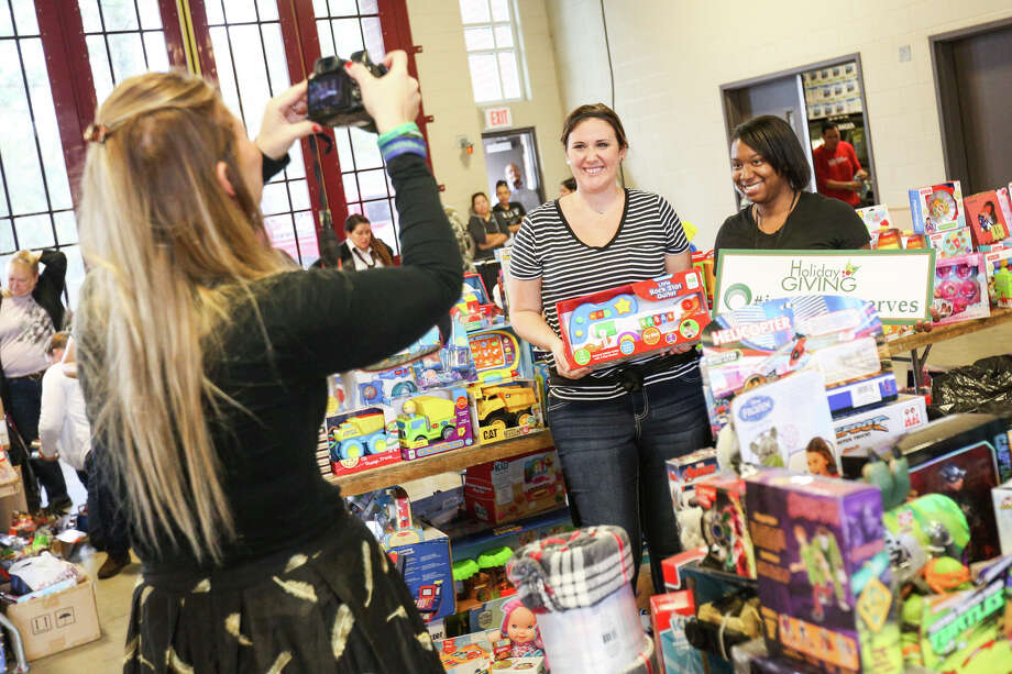 The Woodlands resident Brittinni Glaspie poses for a photo with Aon volunteer Melissa Tucker during Interfaith's holiday toy station on Tuesday, Dec. 13, 2016, at The Woodlands Central Fire Station. Photo: Michael Minasi, Staff / © 2016 Houston Chronicle