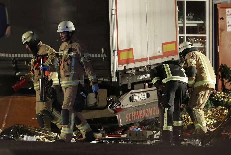 Firefighters inspect the scene where a truck crashed into a crowded Christmas market in the heart of West Berlin, in what police believe was an attack. Photo: Michael Sohn, Associated Press