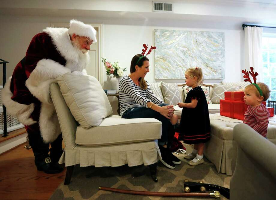 Santa sings to Jennifer Roane and her daughter, Emma, in their home on Saturday, Dec. 17, 2016. (Annie Mulligan / Freelance) Photo: Annie Mulligan, Freelance / @ 2016 Annie Mulligan & the Houston Chronicle