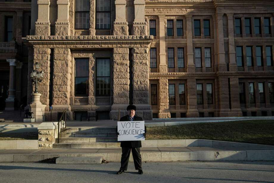 Raymon Daniel holds a sign encouraging electors to vote their conscience on the South steps of the Texas State Capitol in Austin on Monday, Dec. 19, 2016. (AP Photo/Tamir Kalifa) Photo: Tamir Kalifa, FRE / FR170773 AP
