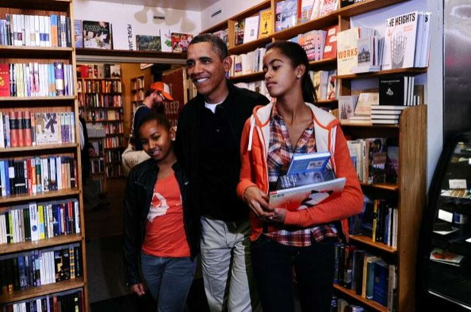 President Obama shops with his daughters Sasha, left, and Malia, at Kramerbooks and Afterwords, a bookstore in Washington, D.C., in 2011. Photo: Jewel Samad / AFP / Getty Images