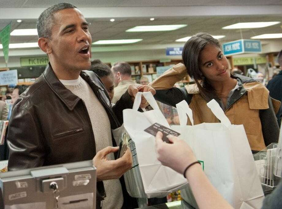 President Obama pays for books with his daughters Sasha, left, and Malia at Politics and Prose bookstore in Washington, D.C., in 2013. Photo: Nicholas Kamm / AFP / Getty Images