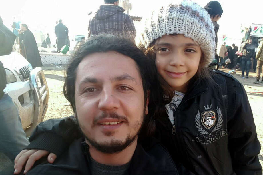 A worker takes a selfie with 7-year-old Bana al-Abed after she was evacuated from the divided Syrian city of Aleppo on Monday. Bana has become known for posting a tragic account of the war on Twitter. Photo: BURAK KARACAOGLU, Stringer / AFP