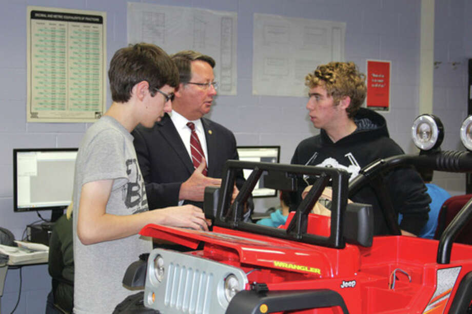 Bad Axe High School senior Johathan Steinbis (left) and Laker High School senior Matthew Bowen (far right) show U.S. Sen. Gary Peters a self-driving model Jeep on Monday in the Mechanical, Architectural, Engineering and Design class offered at the Huron Area Tech Center in Bad Axe.