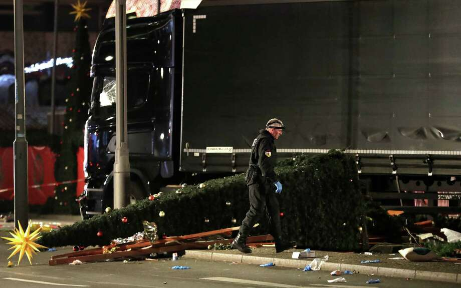 "A police officer investigates the scene after a truck plowed into a popular Christmas market in Berlin on Monday. The White House condemned ""what appears to have been a terrorist attack."" Photo: Michael Sohn, STF / Copyright 2016 The Associated Press. All rights reserved."