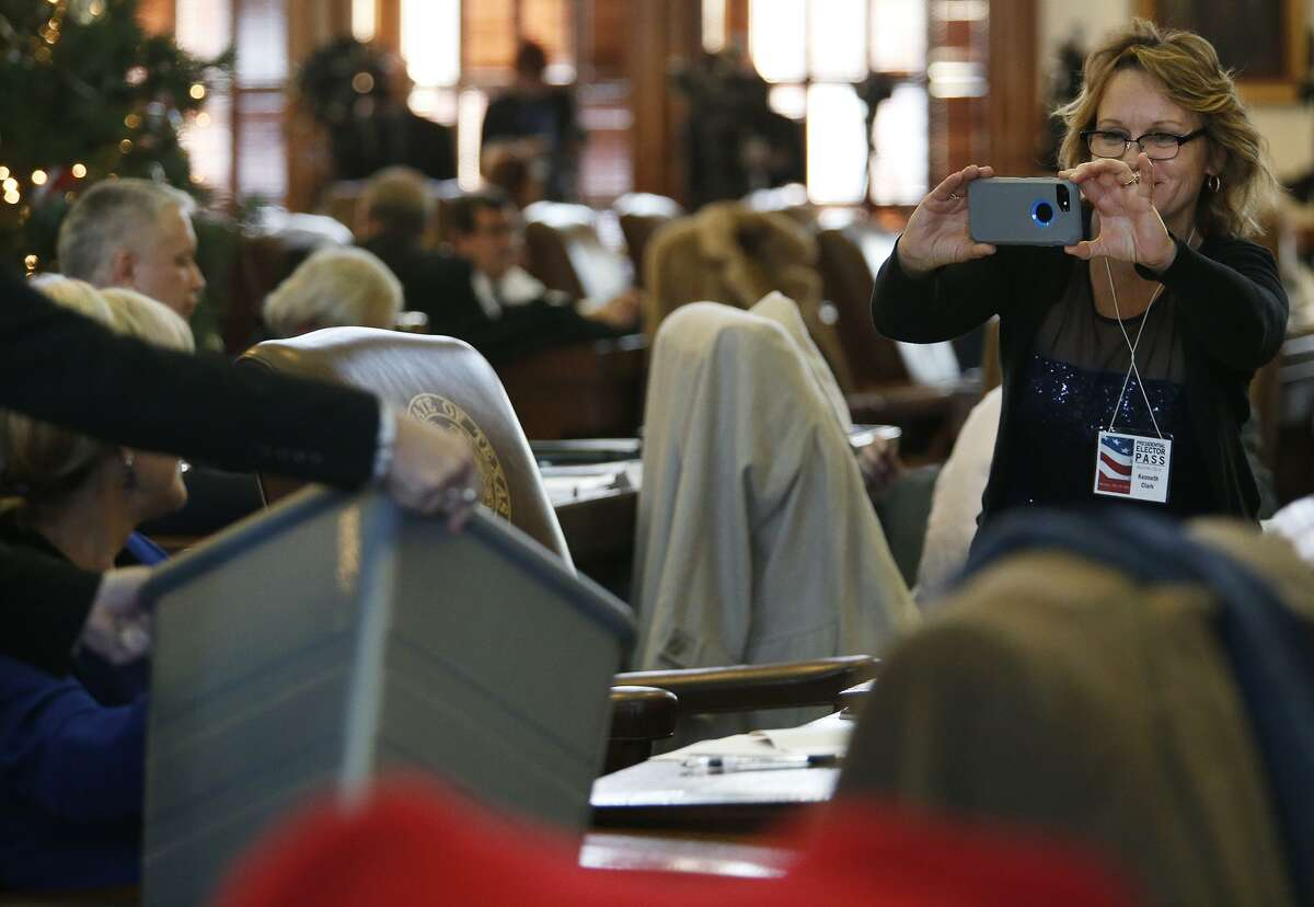A Texas Electoral College elector photographs a colleague casting a ballot in in Austin on Dec. 19, 2016. Federal lawsuits have been filed in four states, including Texas, that contest the winner-take-all method that states use to allocate their Electoral College votes.