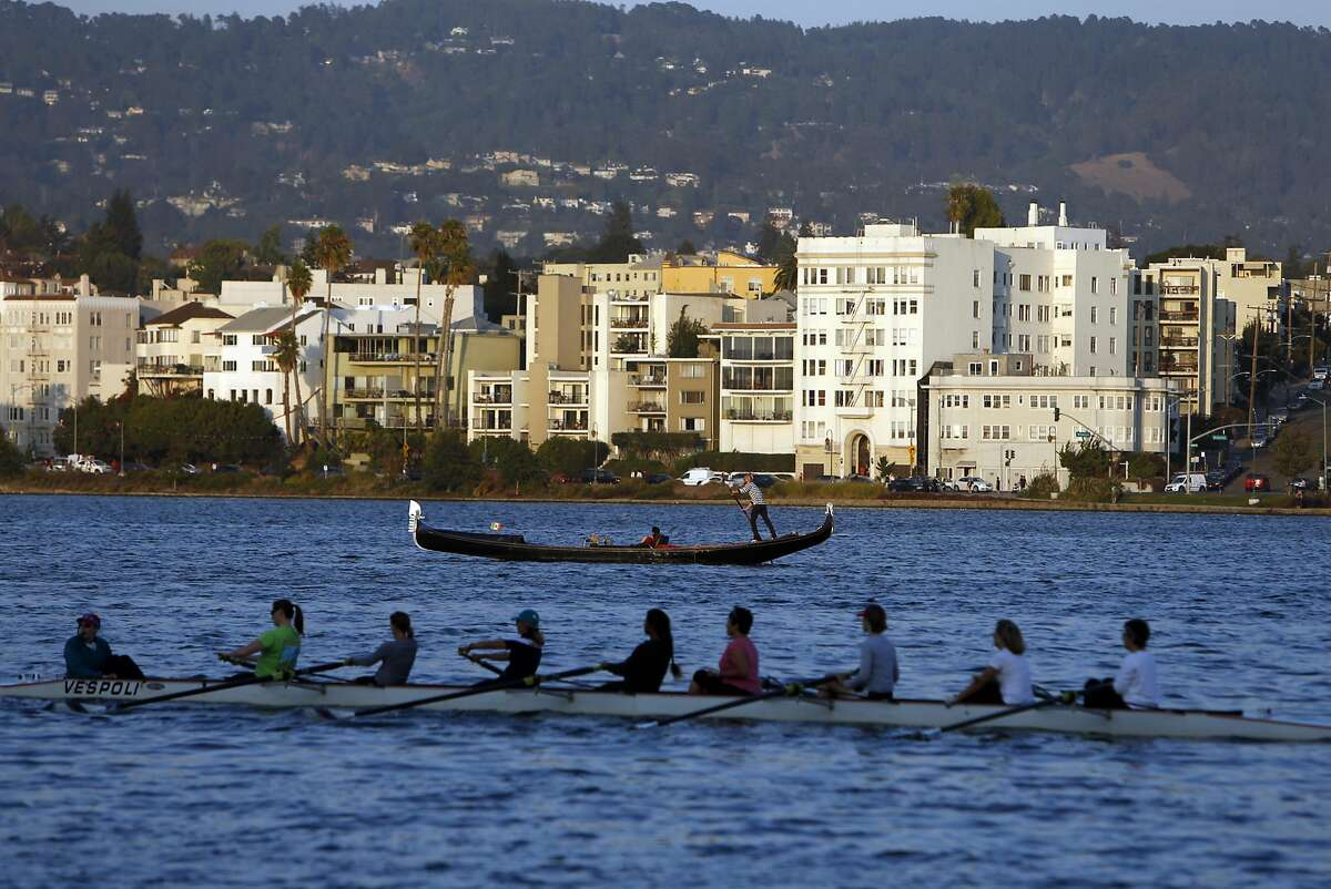 A gondola from Gondola Servizio and an 8 person shell from the Lake Merritt Rowing Club share the water on Lake Merritt in Oakland, Calif. on Wednesday, September 10, 2014.