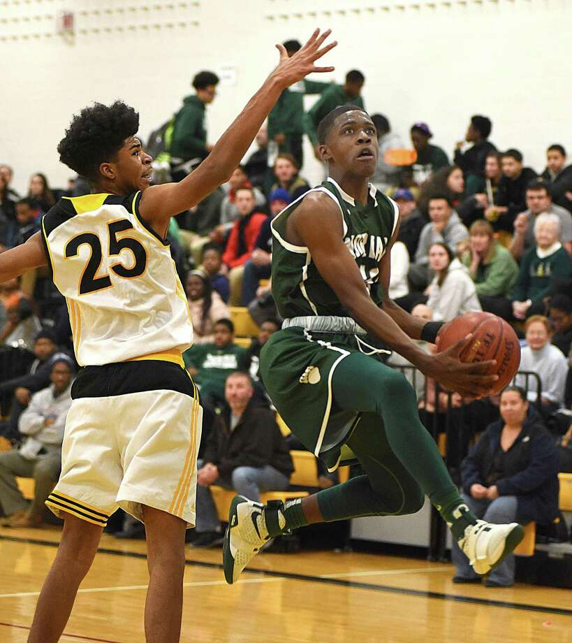 Norwalk High's Armani Sawyer, right, flies past Kaynor Tech's Zachary Jules for a lay-up during the first half of Monday's season opening game in Waterbury. Norwalk won the game 78-39. Photo: John Nash