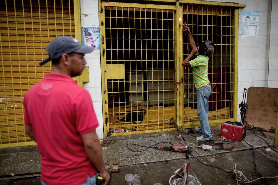 A store owner repairs the security gate at the entrance to his grocery store looted by demonstrators the night before, in Ciudad Bolivar, Venezuela, Monday, Dec. 19, 2016. Last week, President Nicolas Maduro made an announcement annulling all 100-bolivar notes leading to massive lines at banks, and cash transactions such as buying food or gasoline extremely difficult. Maduro suddenly changed course late Saturday, announcing the 100-bolivar notes could be used until Jan. 2. Before that announcement riots and looting broke out in several cities. (AP Photo/Alejandro Cegarra) Photo: Alejandro Cegarra, STR / Copyright 2016 The Associated Press. All rights reserved.