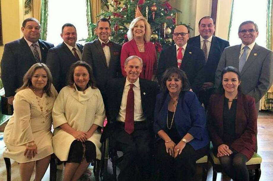 Invitees to a recent luncheon at the Texas governor's mansion pose for a photo with Gov. Greg Abbott, seated center, and his wife, Cecilia Abbott, seated at his right. Miguel Conchas, president of the Laredo Chamber of Commerce, is pictured standing on the far right. Photo: Courtesy Photo
