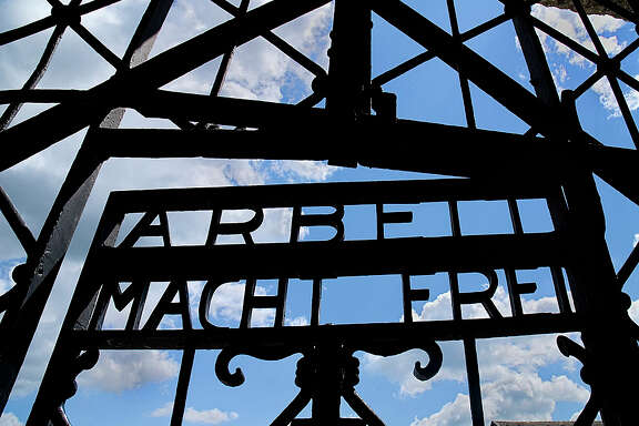 "Gate at the Dachau concentration camp in Germany. The slogan  ""Arbeit Macht Frei"" means ""Freedom Through Work."""