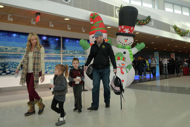 Summers Halgren, left, of West Memorial, and her husband, Chris, right, lead their children, June, 3, and Colton, 5, from the Southwest Airlines terminal at Hobby Airport in Houston on Tuesday, Dec. 20, 2016. The Halgrens were on their way to Winterpark, CO, for the Christmas holidays. (Photo by Jerry Baker/Freelance)