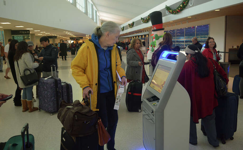 Debra Cobb of Friendswood works the bag tag machine Tuesday in the Southwest Airlines terminal at Hobby Airport. Photo: Jerry Baker, Freelance / Freelance