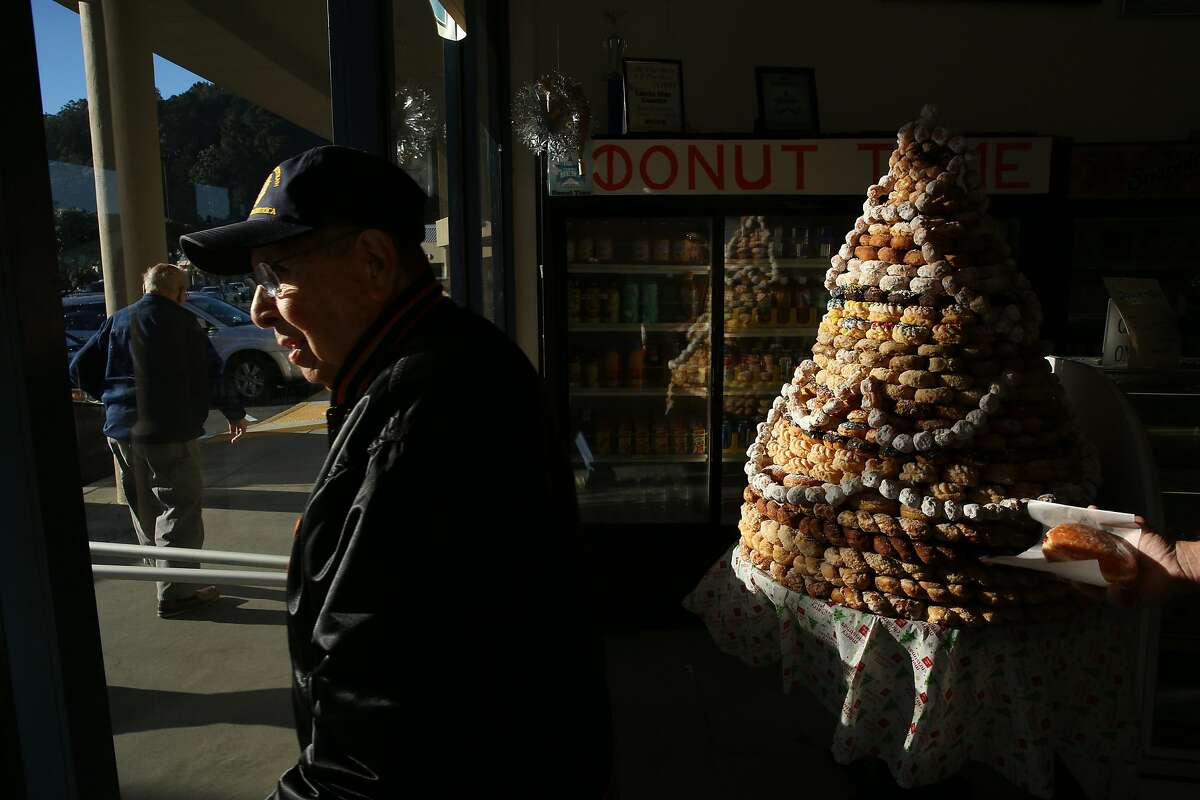 From left: Ed Raffo, Vern Alonzo and Robert Roach (carrying a jelly filled donut) head out of Donut Time on Tuesday, Dec. 20, 2016 in Pacifica, Calif. The longtime donut shop, located at 1235 Linda Mar Shopping Center, is set to lose its lease and close in January. Raffo and Alonzo, both of Pacifica, said they've regularly visited the shop for more than 25 years.